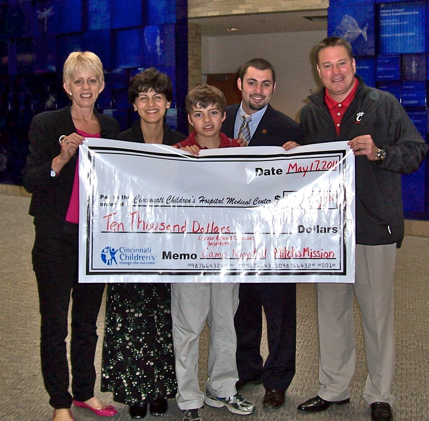 Local foundation, Mitch's Mission, presented a check for $10,000 to Cincinnati Children's.  On hand were Dee Stone, Dr. Mariam Fouladi, an oncologist at Children's, Mitch Stone, Drew Smith, UC Student body President, and Butch Jones, UC Head Football coach.